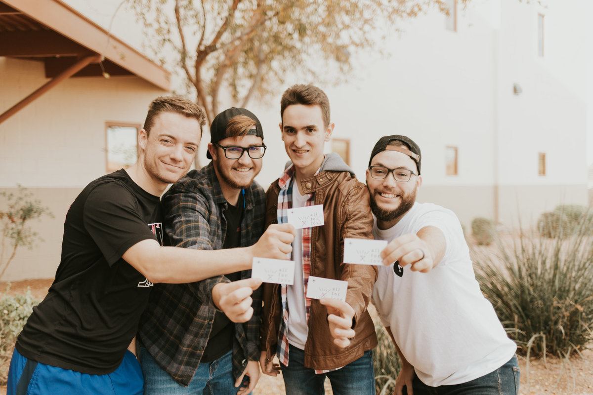 A picture of guys who attend Mission Church holding up Christmas invitation cards.