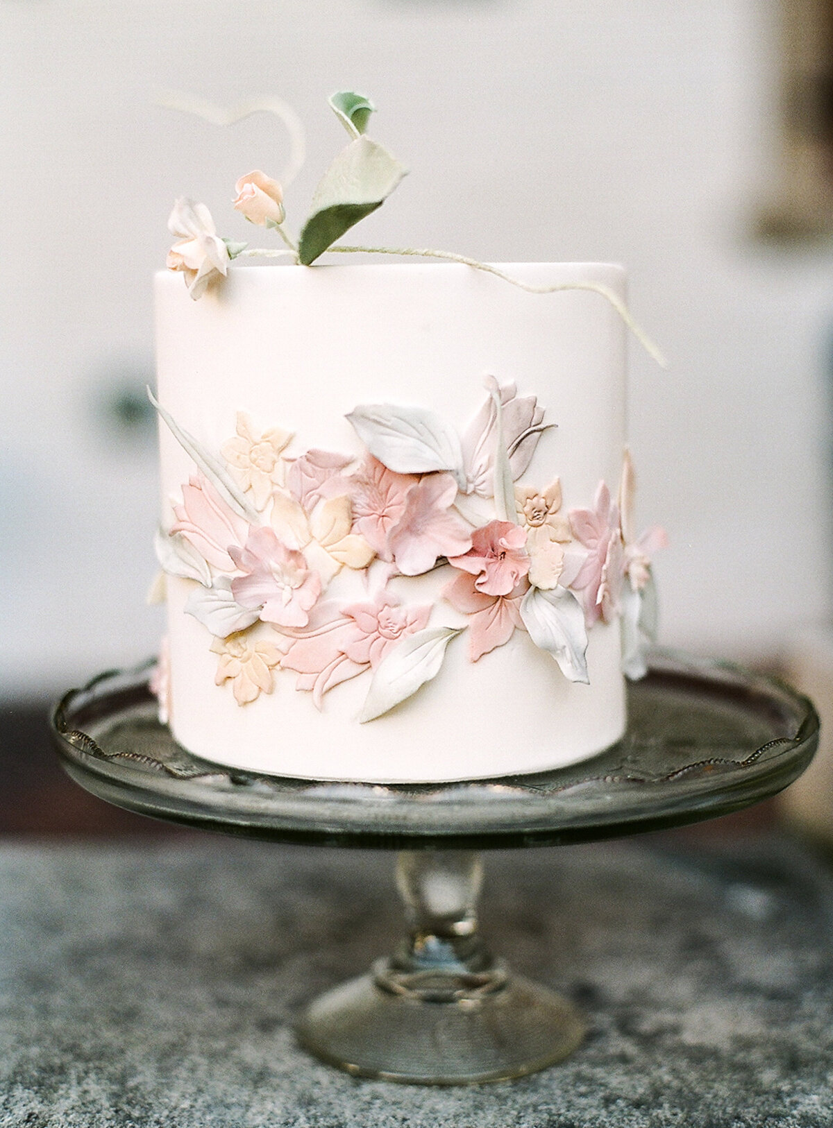 Individual wedding cake on stand and decorated with flowers