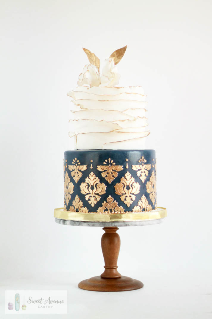 white and navy blue wedding cake with gold damask and ruffles