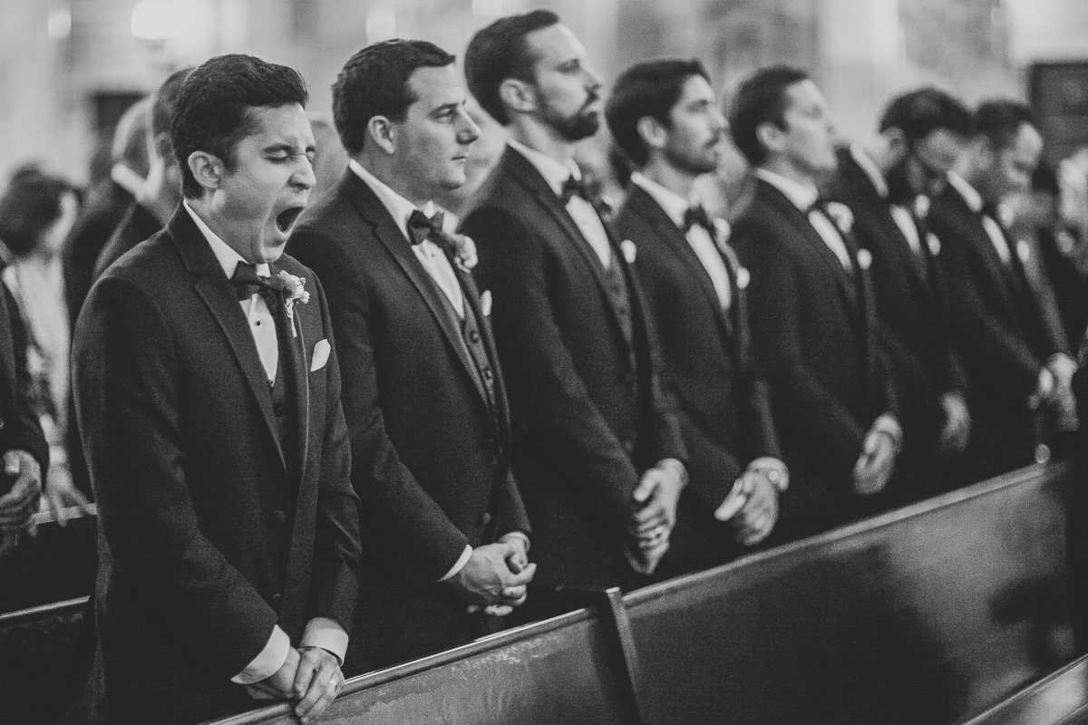 Groomsman yawns during catholic ceremony in Pasadena, Ca.