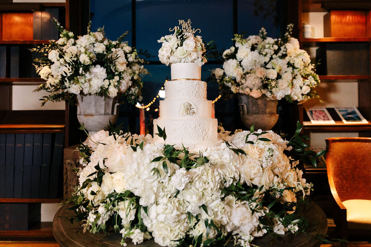 White four tiered wedding cake surrounded by florals at Dallas Arboretum wedding reception