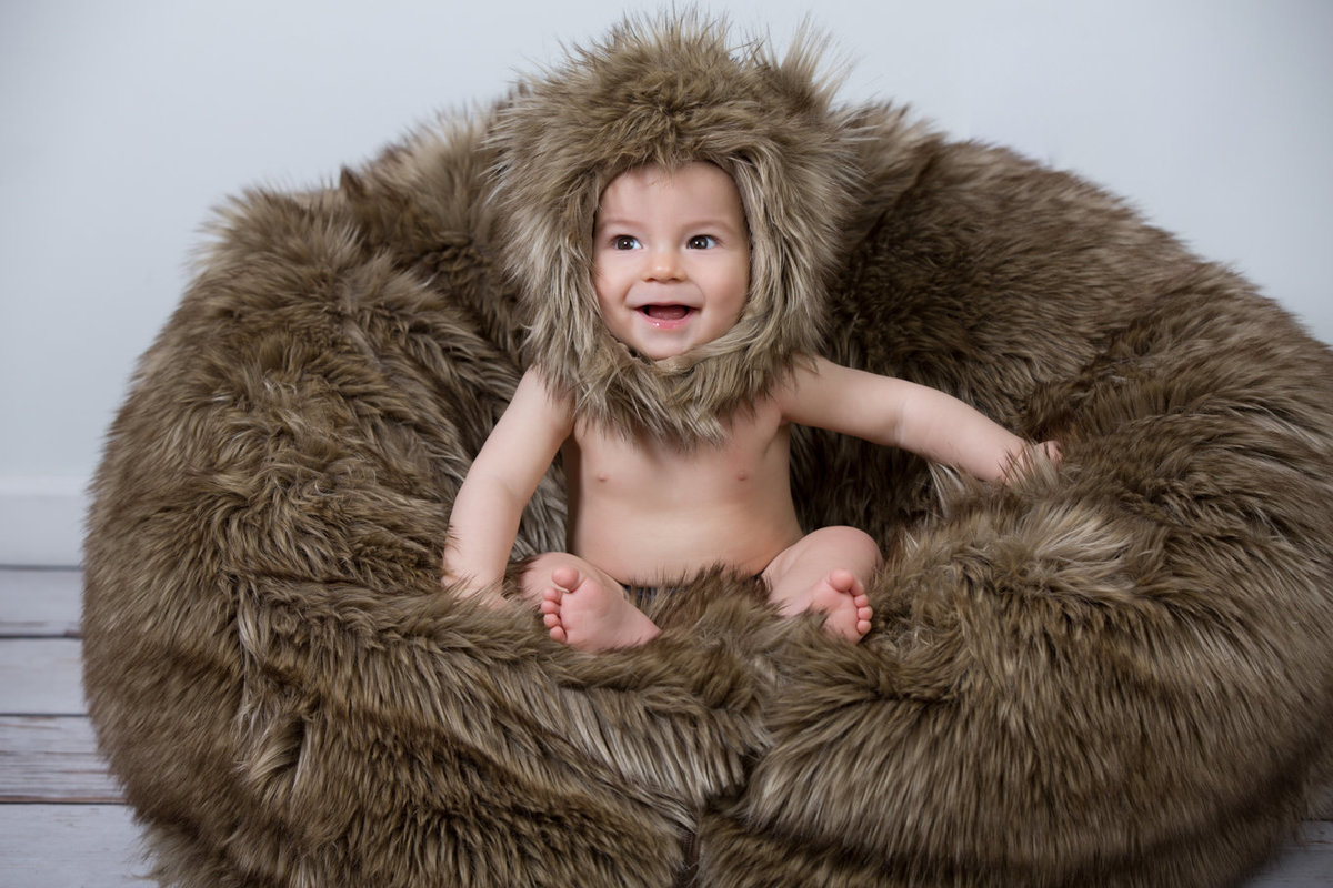 Baby with Fur Pillow and Hat in Studio