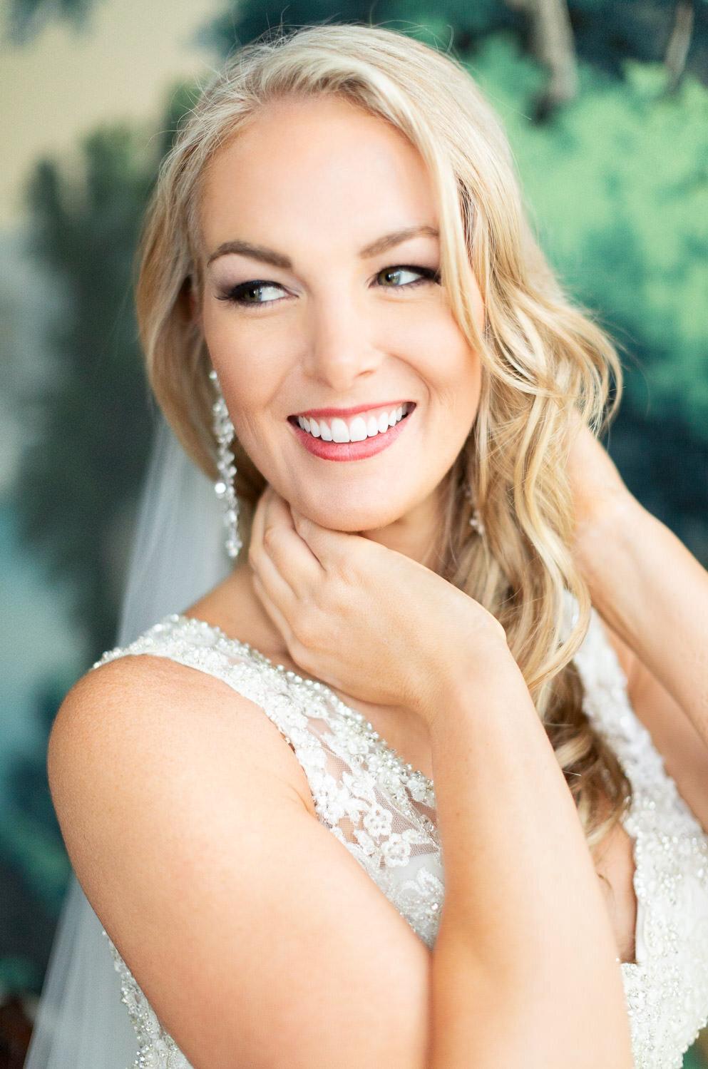 blond bride smiling with hands on neck in wedding dress  green background