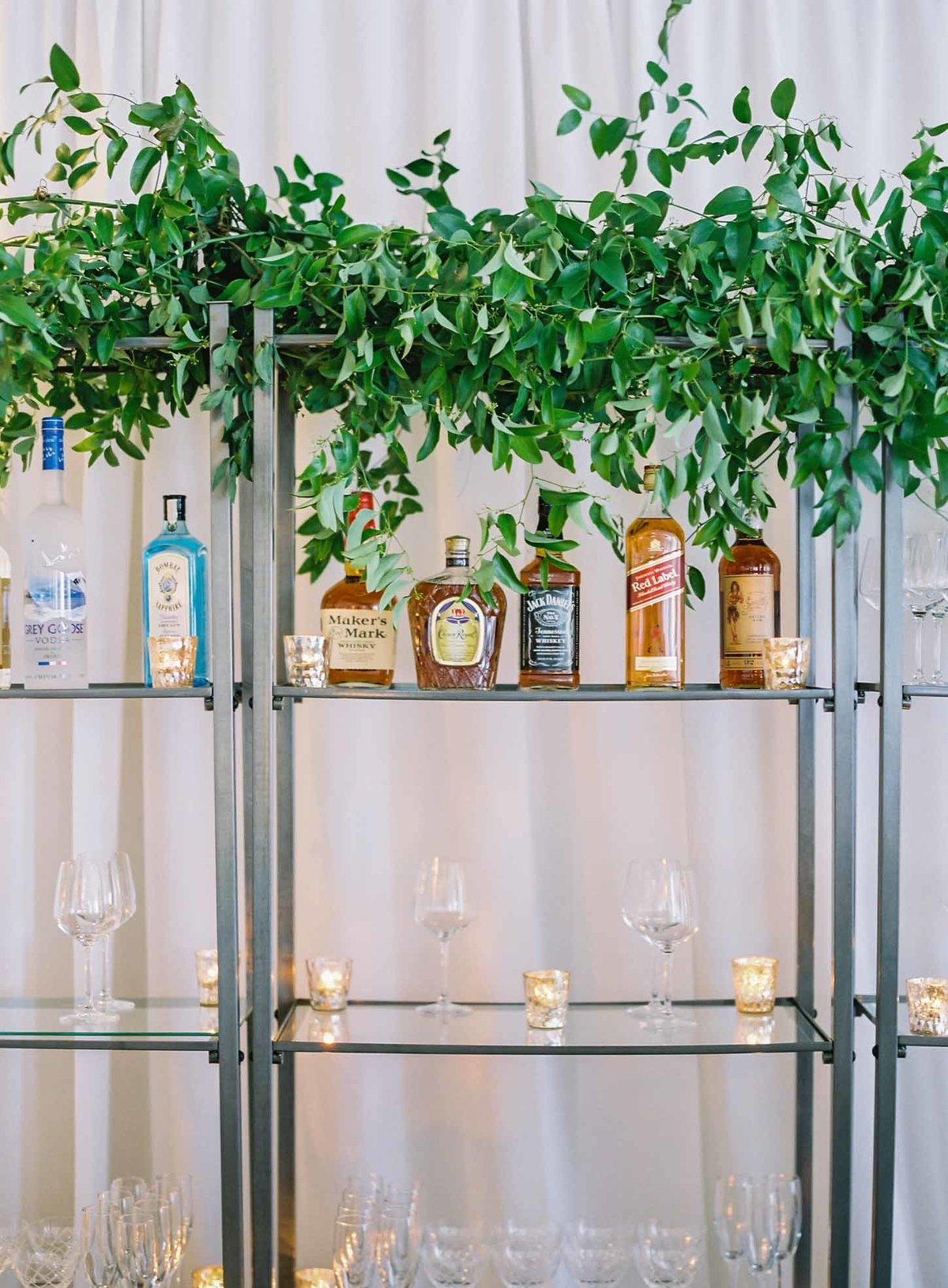 Wedding reception bar shelves covered in green vines and glowing with candle light is so romantic.