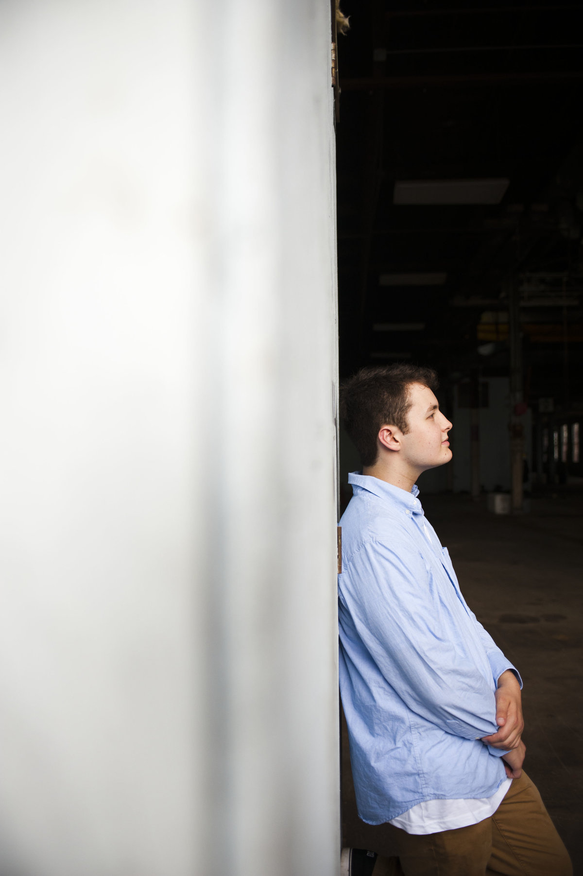 High school boy leans against a wall on profile for senior portrait in downtown Portland, Maine