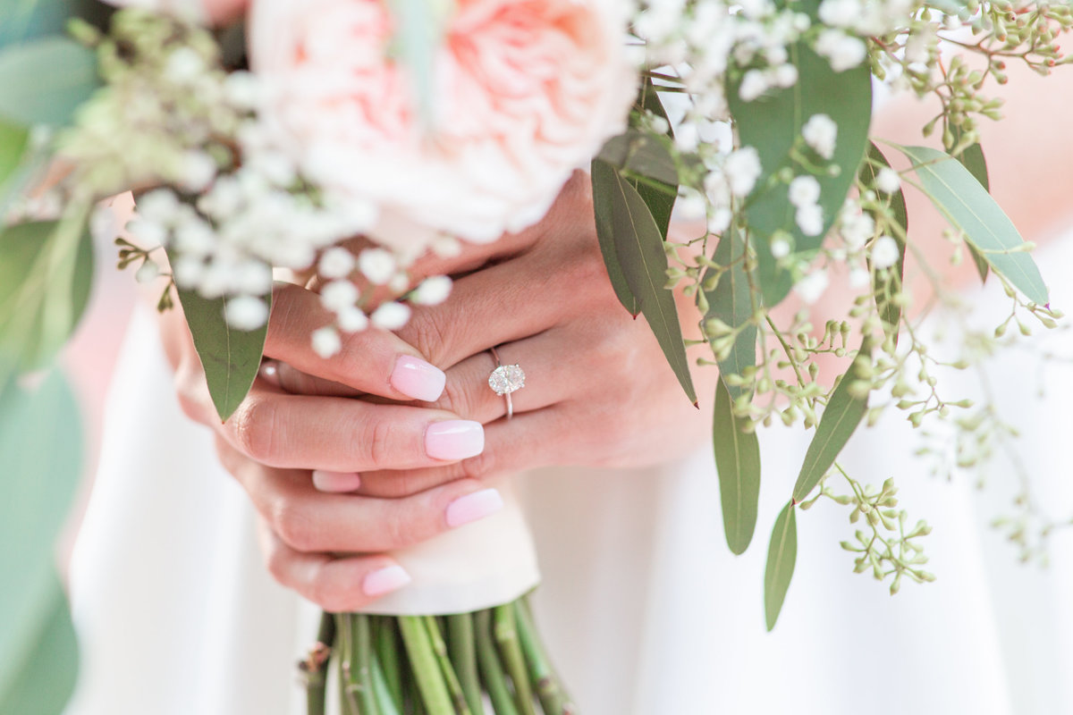 Closeup of an engagement ring worn by a bride holding a bouquet