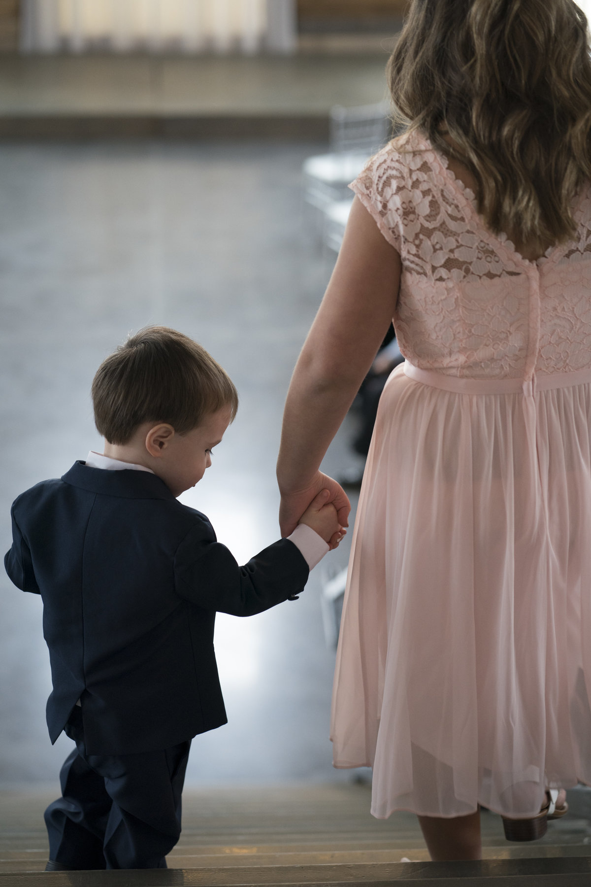 ring bearer holding hands going down stairs, blue haven barn sioux falls, sd.