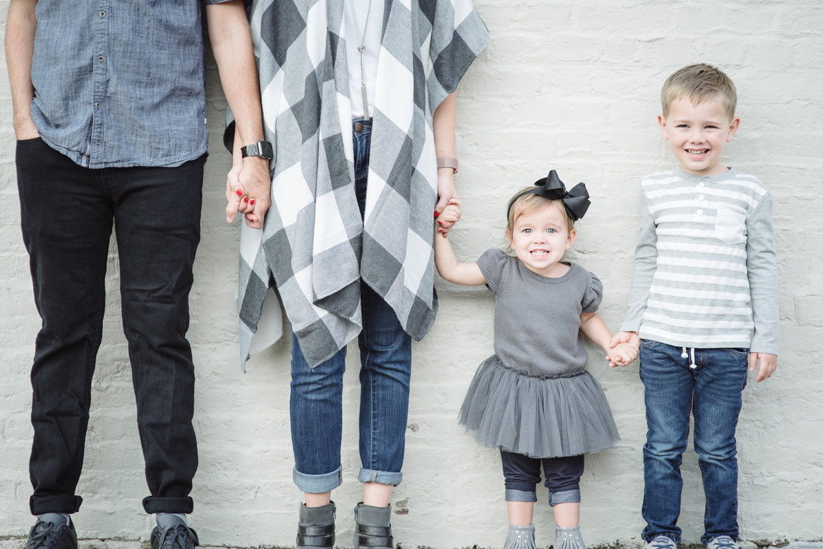 Family of four stands against a white wall in downtown Franklin, TN an d the photographer captures the facial expressions of the son and daughter smiling at the camera