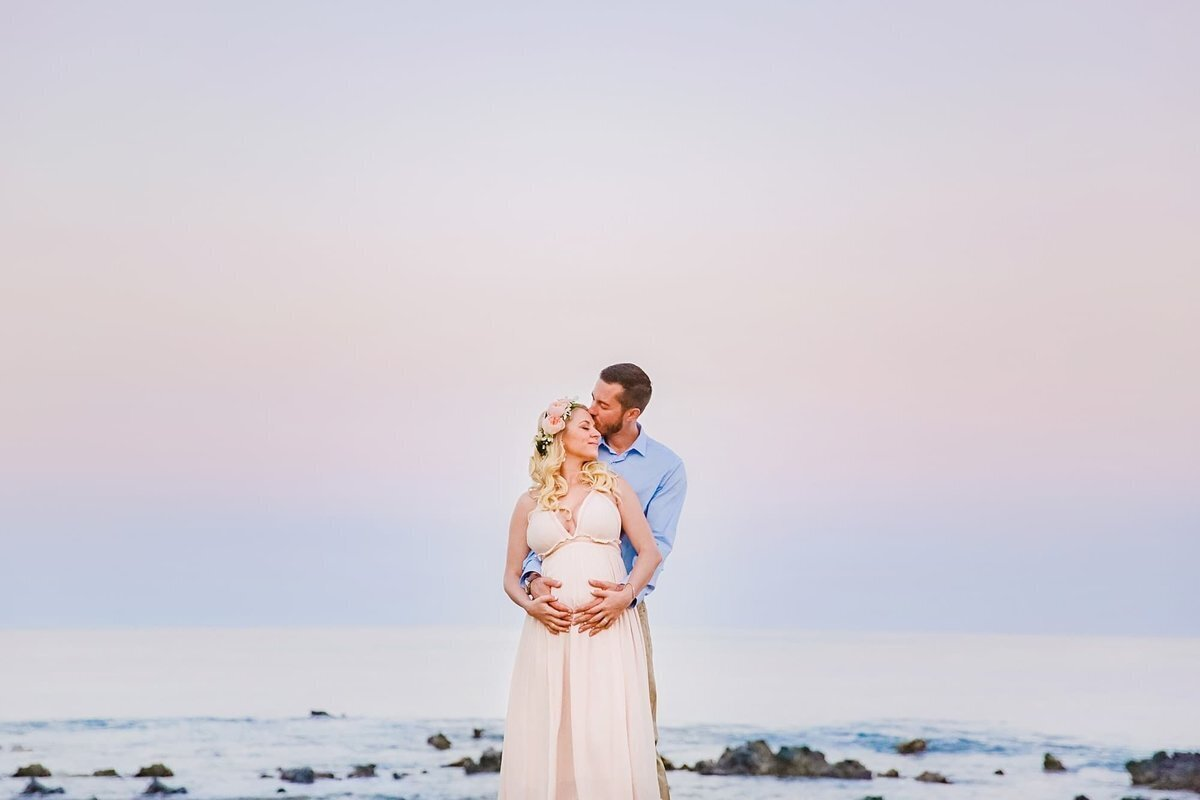Husband kisses pregnant wife's cheek during sunrise Maui portrait session