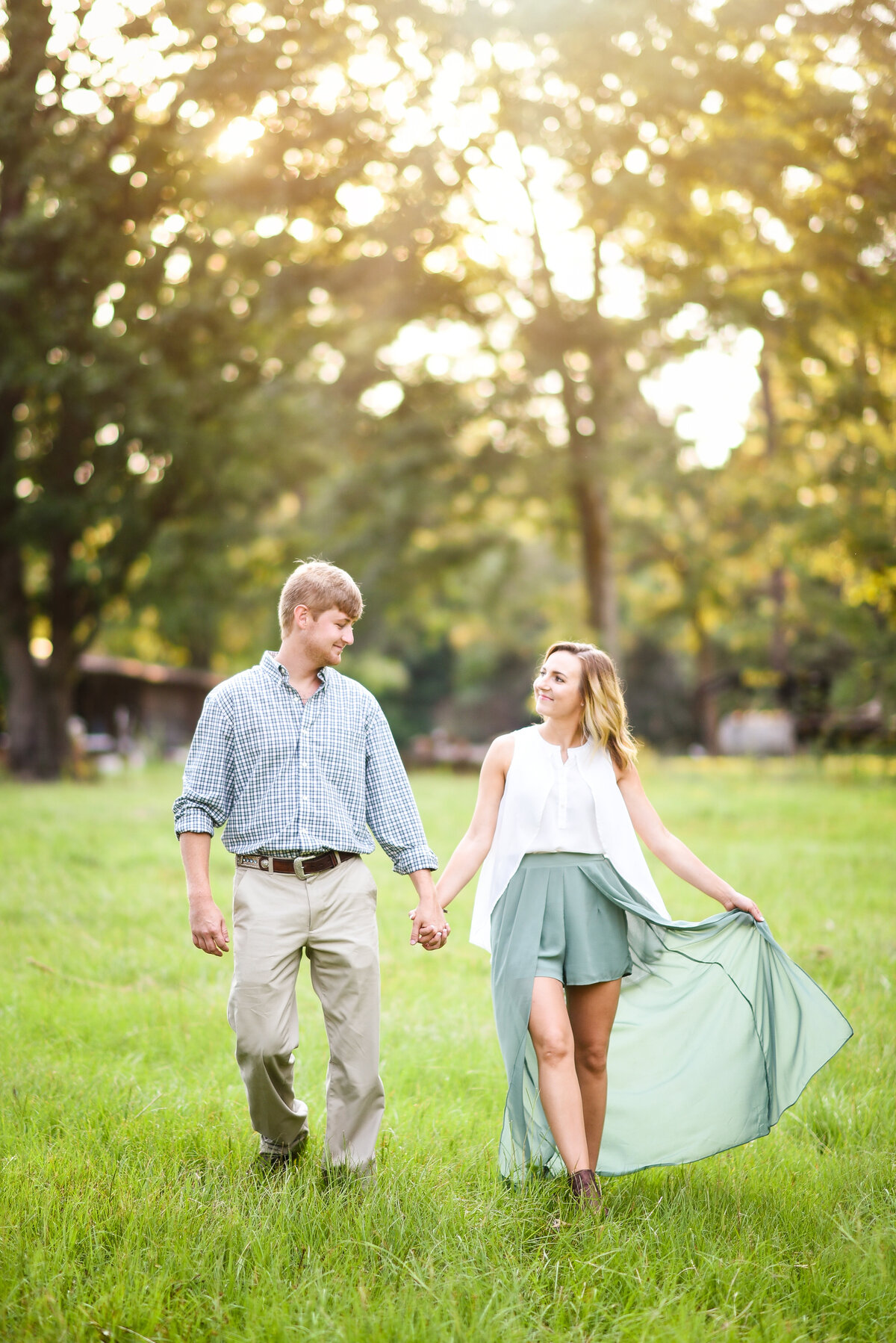 Beautiful Mississippi Engagement Photography: couple walks holding hands in a field during sunset with bride in flowy skirt