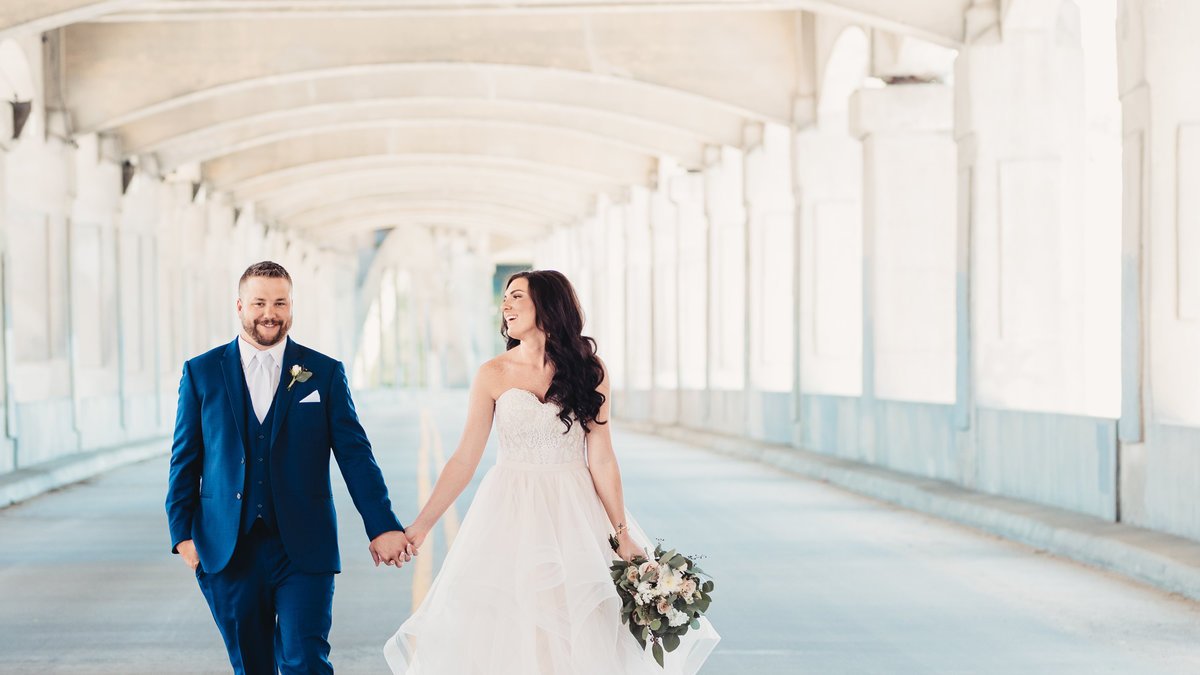 Adam and Katie Perkins walking on the 12th Street Bridge during their Wedding Portraits.