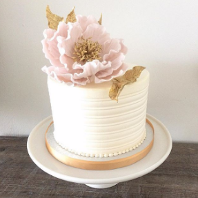 Whippt Desserts cutting cake in buttercream ridges and handmade sugar flower and leaves on top