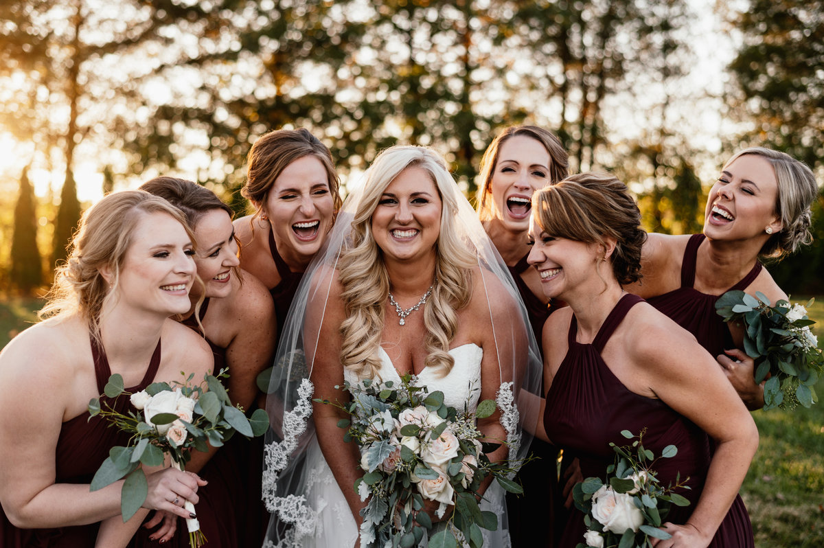 A bride laughs with her bridesmaids