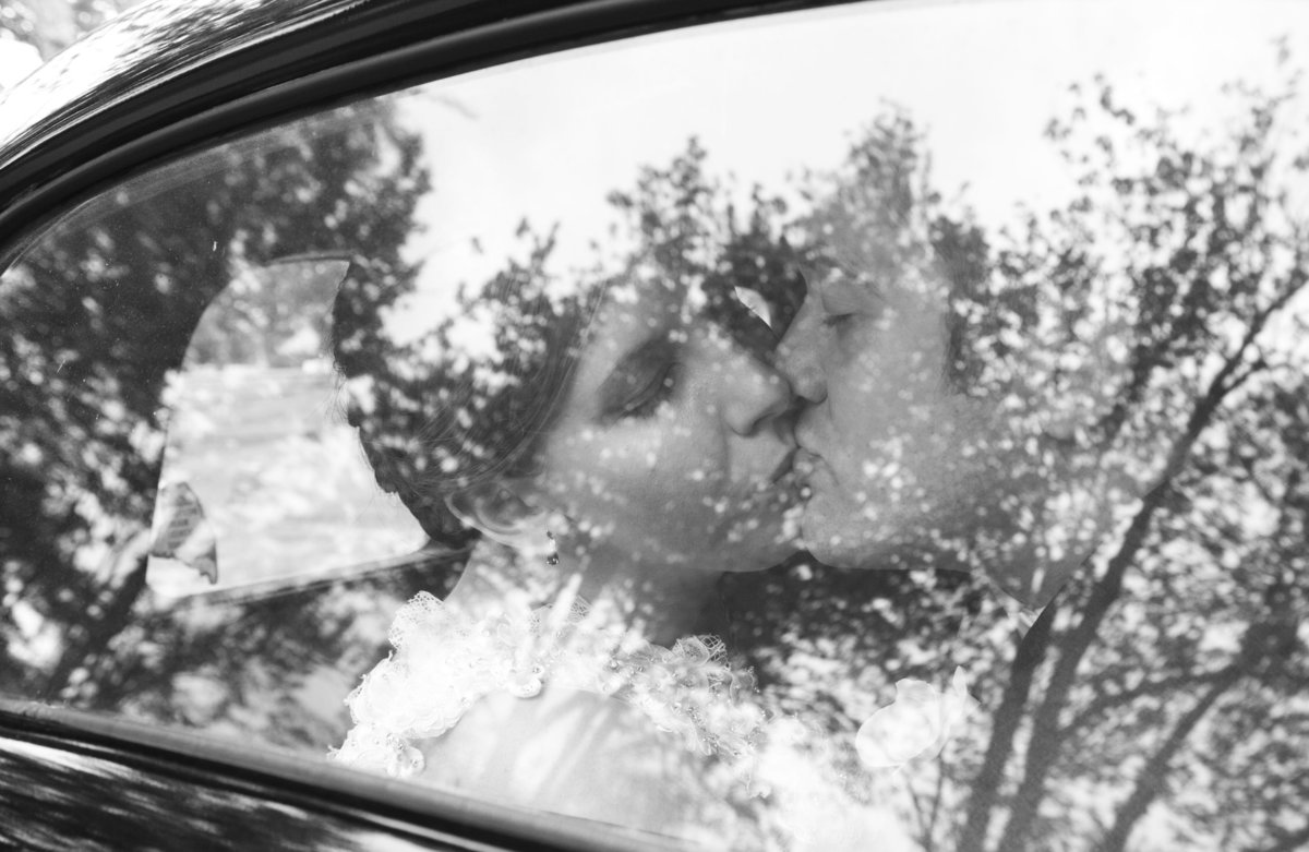 Bride & groom kissing in their wedding getaway car after their Portland, Maine wedding