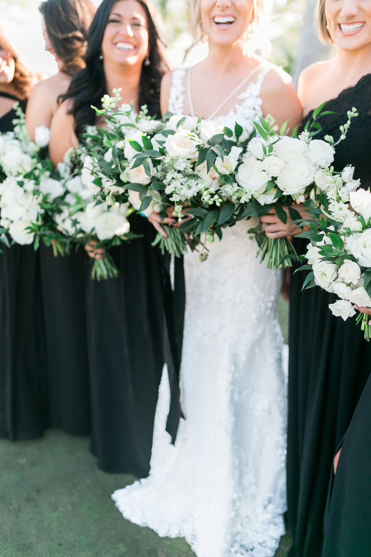 bride and bridesmaids photo in black bridesmaids dresses with white and greenery bouquet with black ribbon