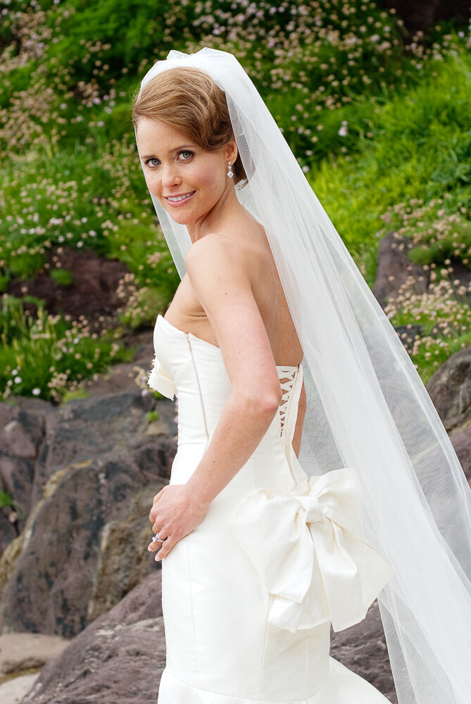 bride wearing a mermaid style wedding dress with corset bodice and large bow with long veil looking over her shoulder while standing on a beach