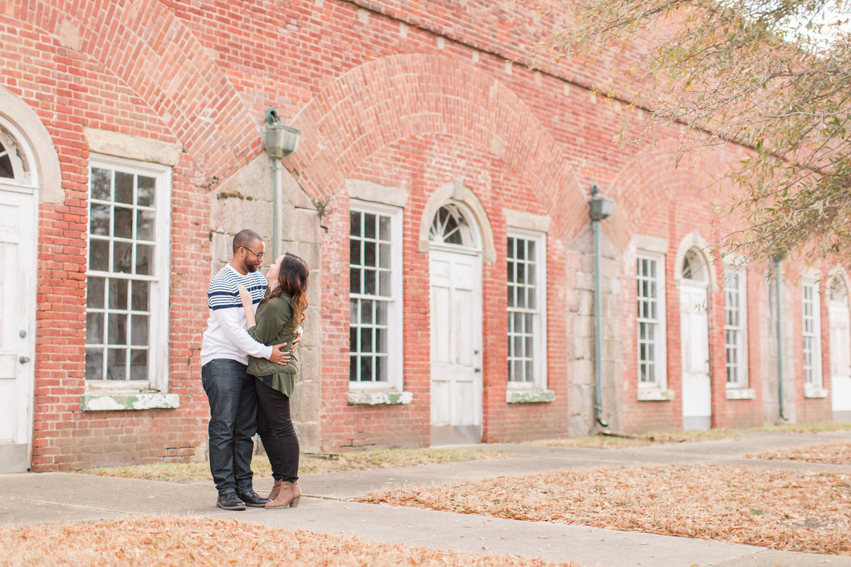 couple embracing in front of brick wall at Fort Monroe