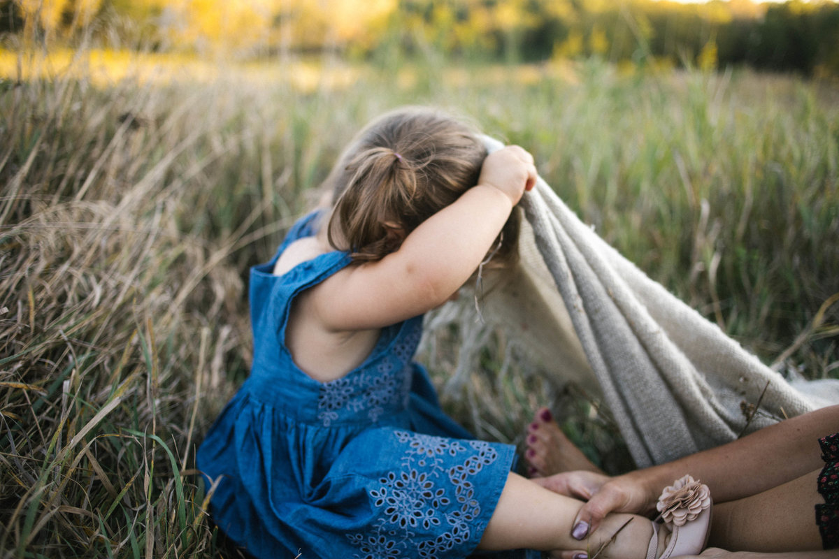 Little girl hiding under a blanket during photo session with Elle Baker Photography