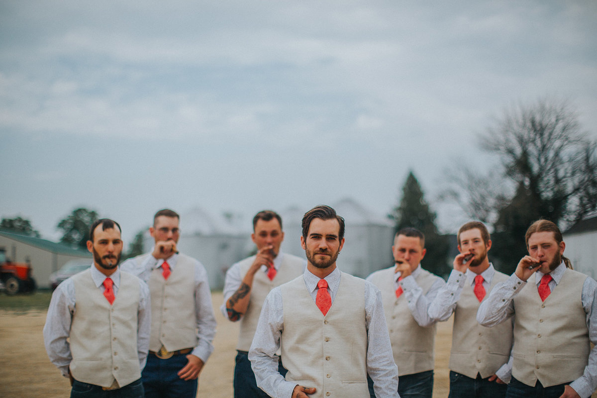 groomsmen smoking cigars on a wedding at williams tree farm in rockford illinois