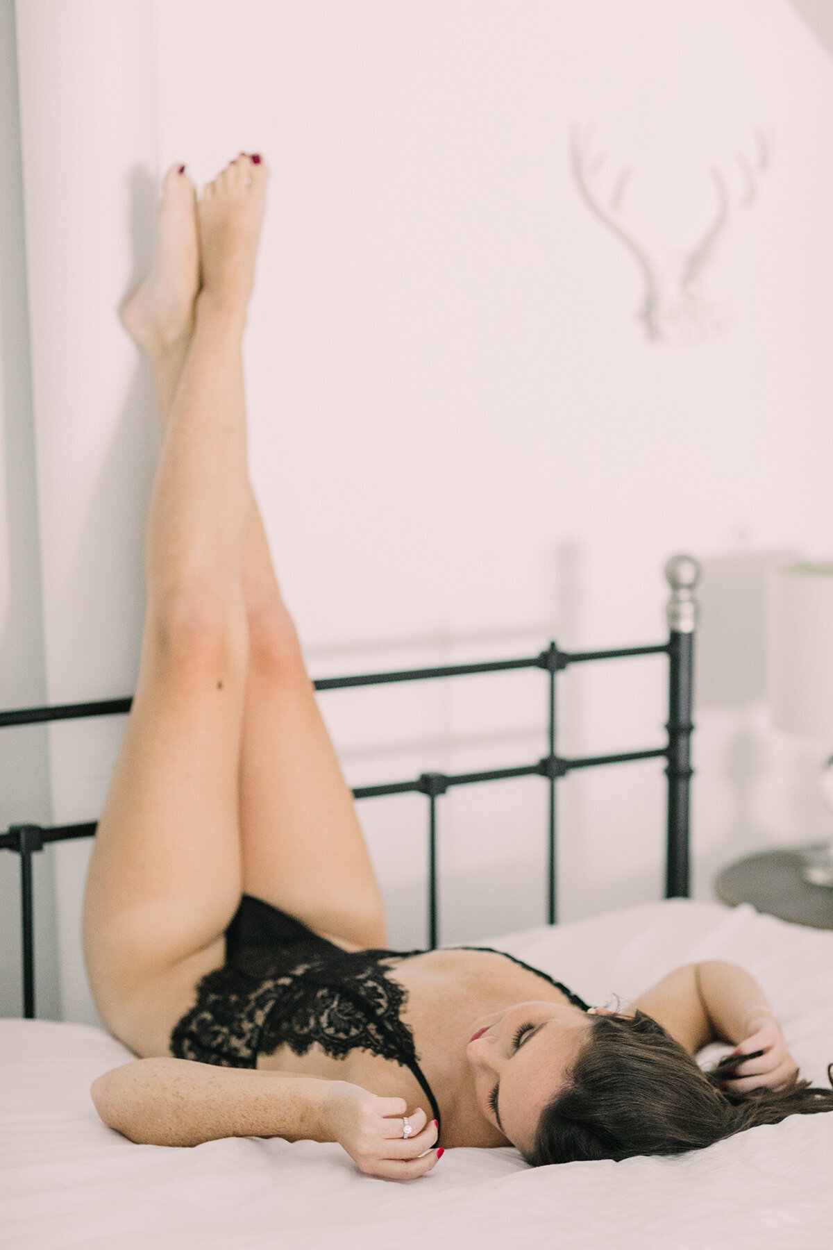 A woman lounging in bed while posing for a boudoir photo