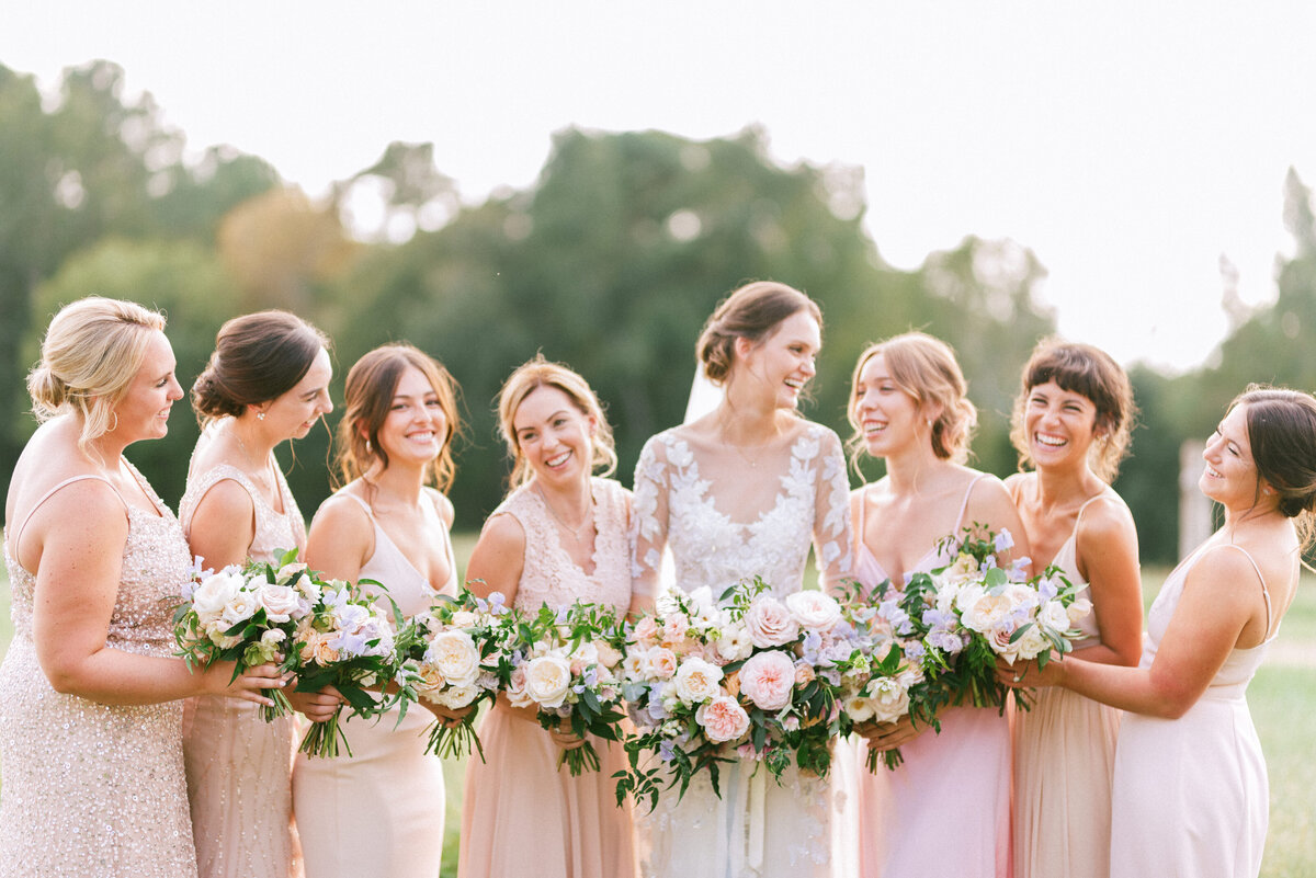 Bride smiles and laughs with her bridesmaids on her wedding day