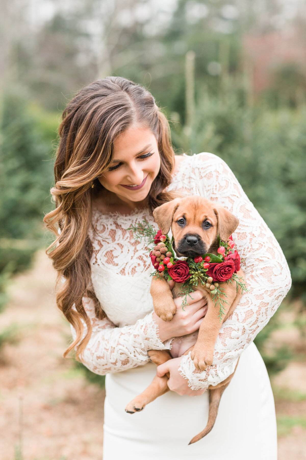 Bride holding an adoptable puppy in a flower collar