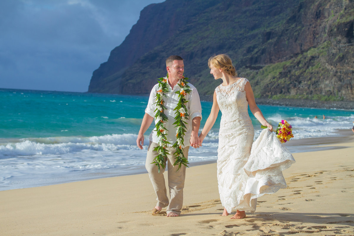 Couple take a walk on the beach during their Hawaiian wedding elopement.
