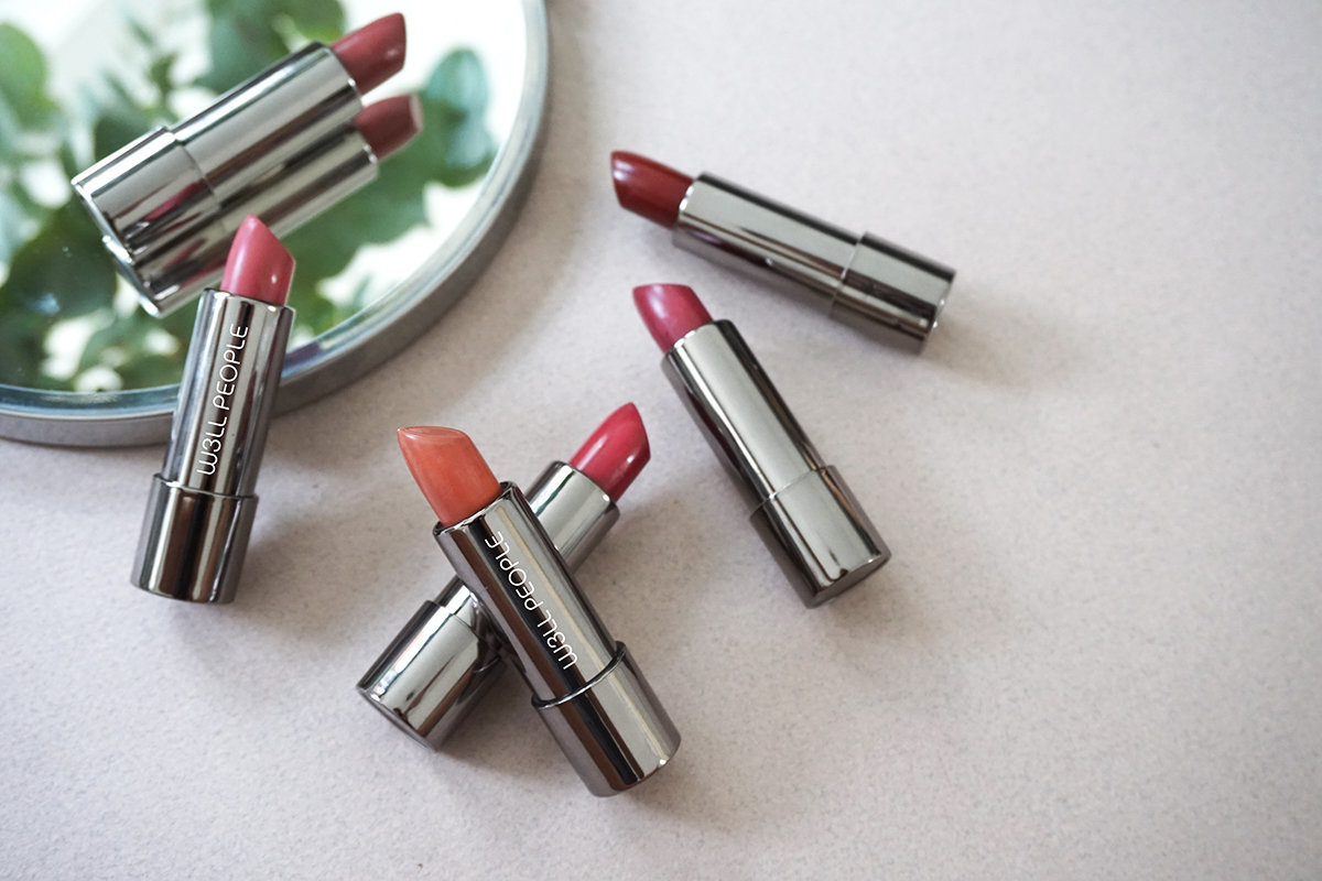 Optimist Lipstick Collection on Greige Background with mirror and greenery