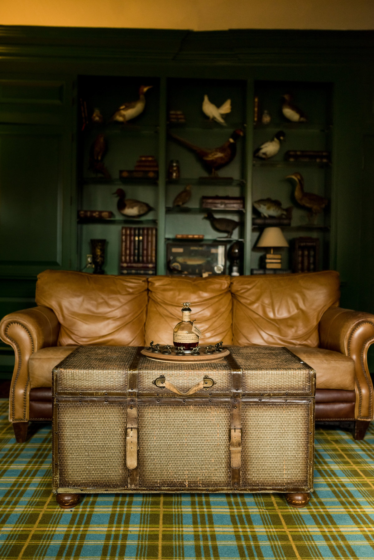 plaid room with leather couch for groomsmen prep in Grand View Estate