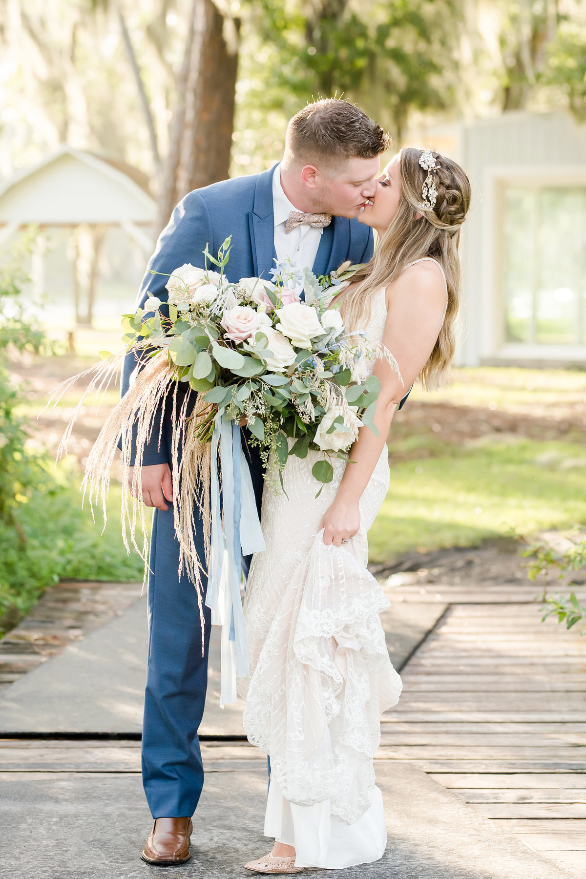 Bride and groom embrace and kiss holding bouquet