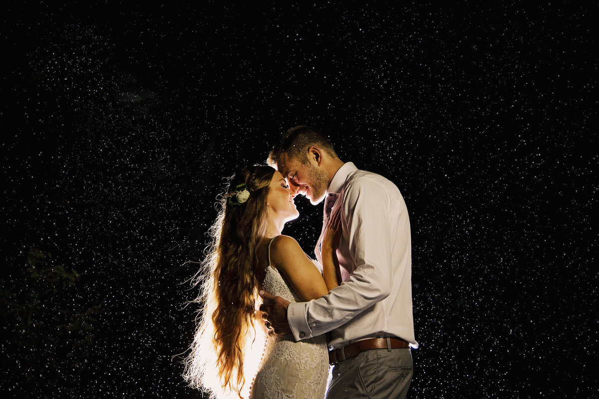 bride and groom kissing in the rain at night in nj wedding
