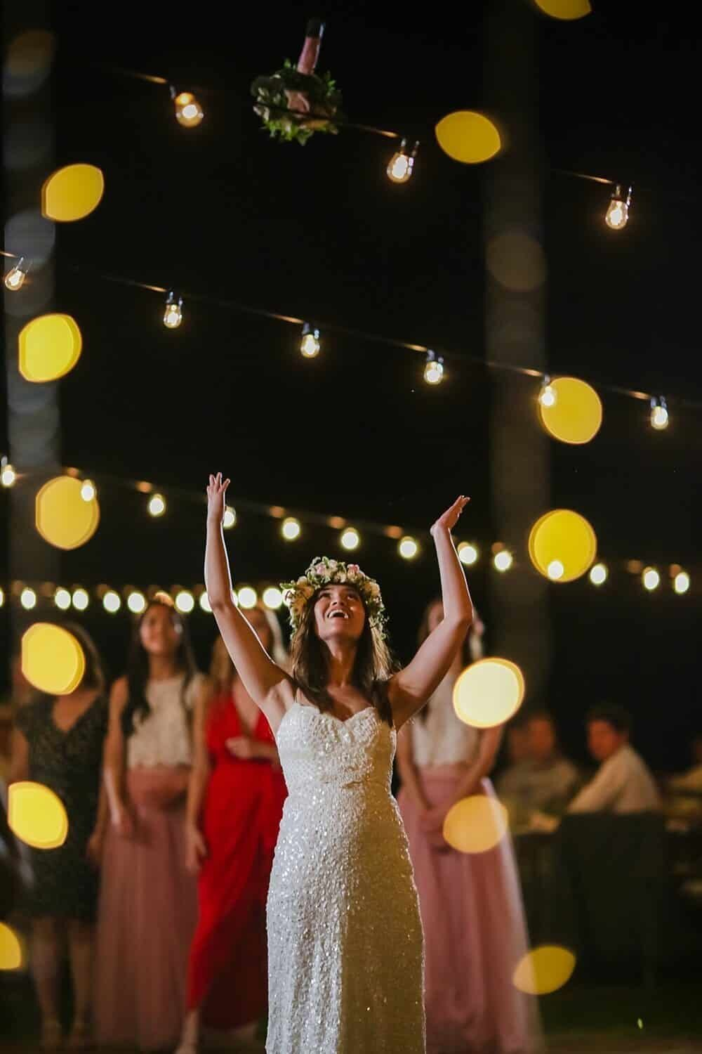 Bride tosses bouquet in the air at her Olowalu Plantation House wedding