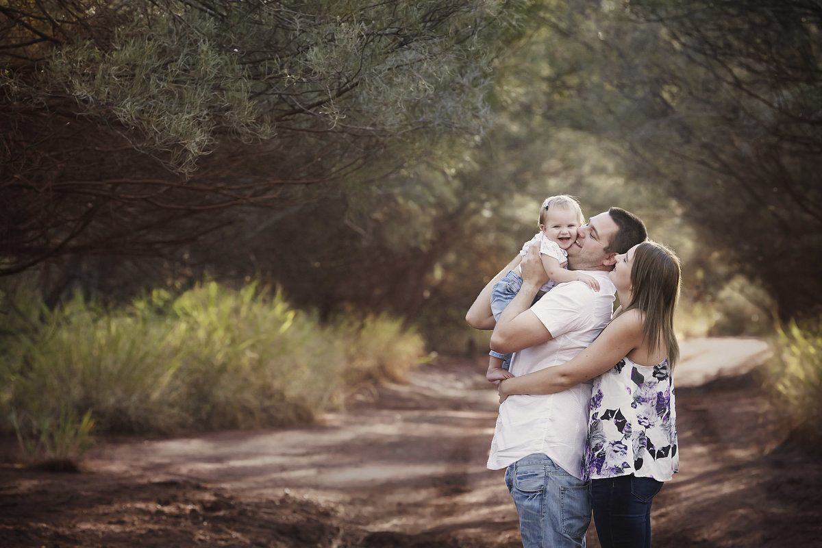 Couple with a baby cuddling into the little girl in natural bushland