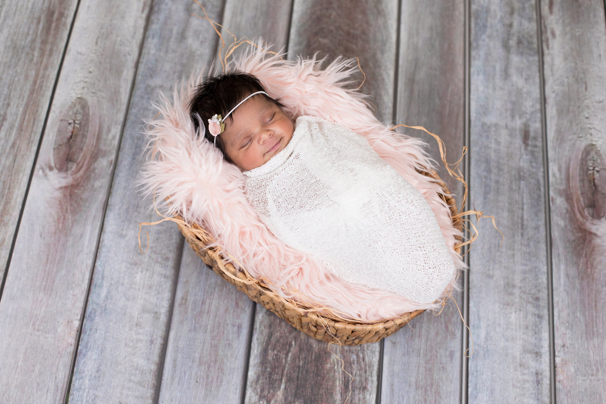 Newborn girl with pink fluffy blanket and she is smiling with her eyes closed