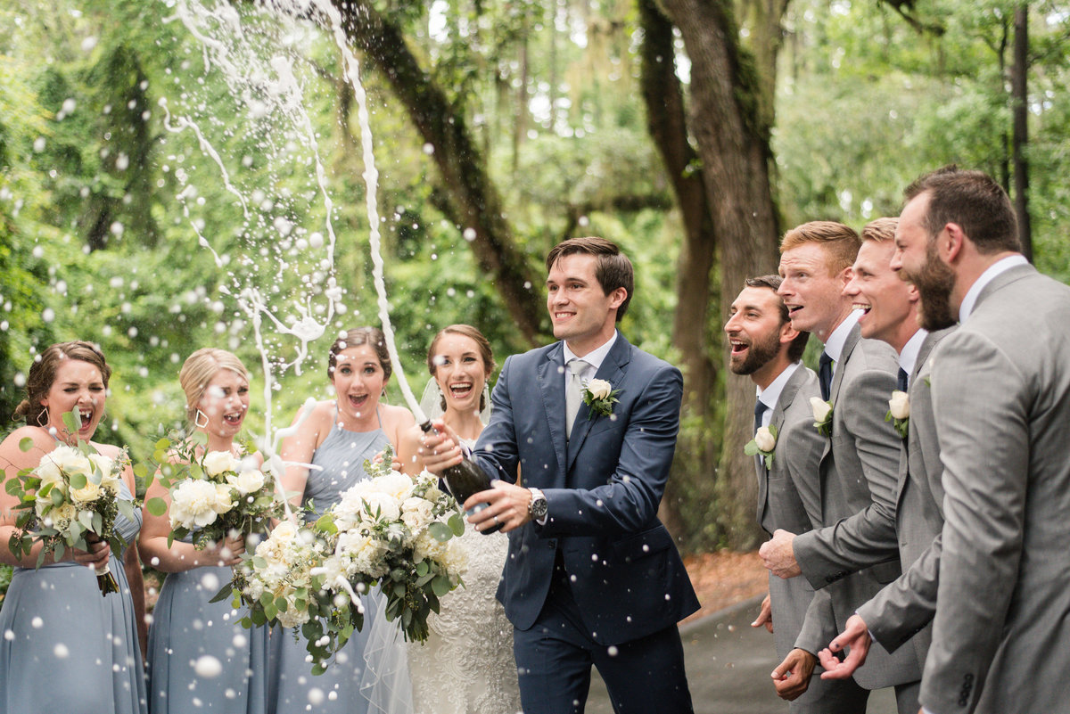 groom popping champagne bottle with bridal party at callawassie island south carolina by virginia wedding photographer