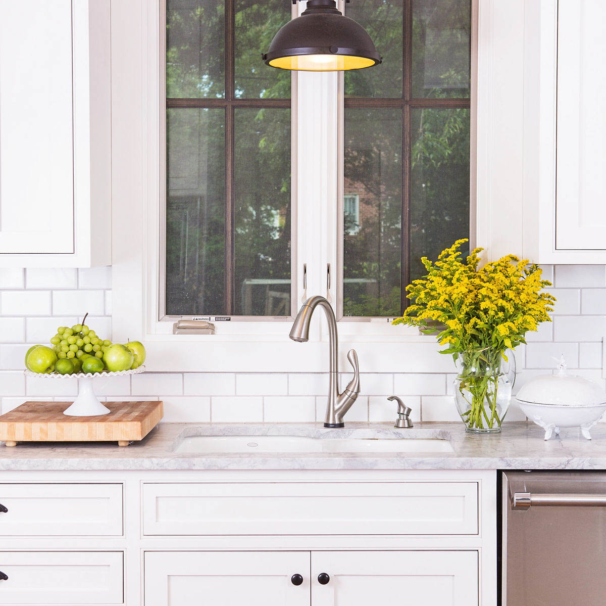 Bright white, clean kitchen, with green apples and vase of yellow flowers on the counter