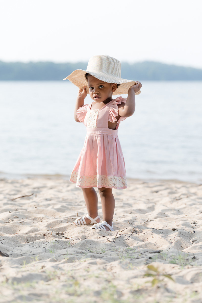 Toddler in a pink dress and sunhat on the beach