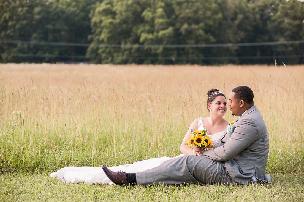 A bride and groom sitting in front of a field in Spotsylvania