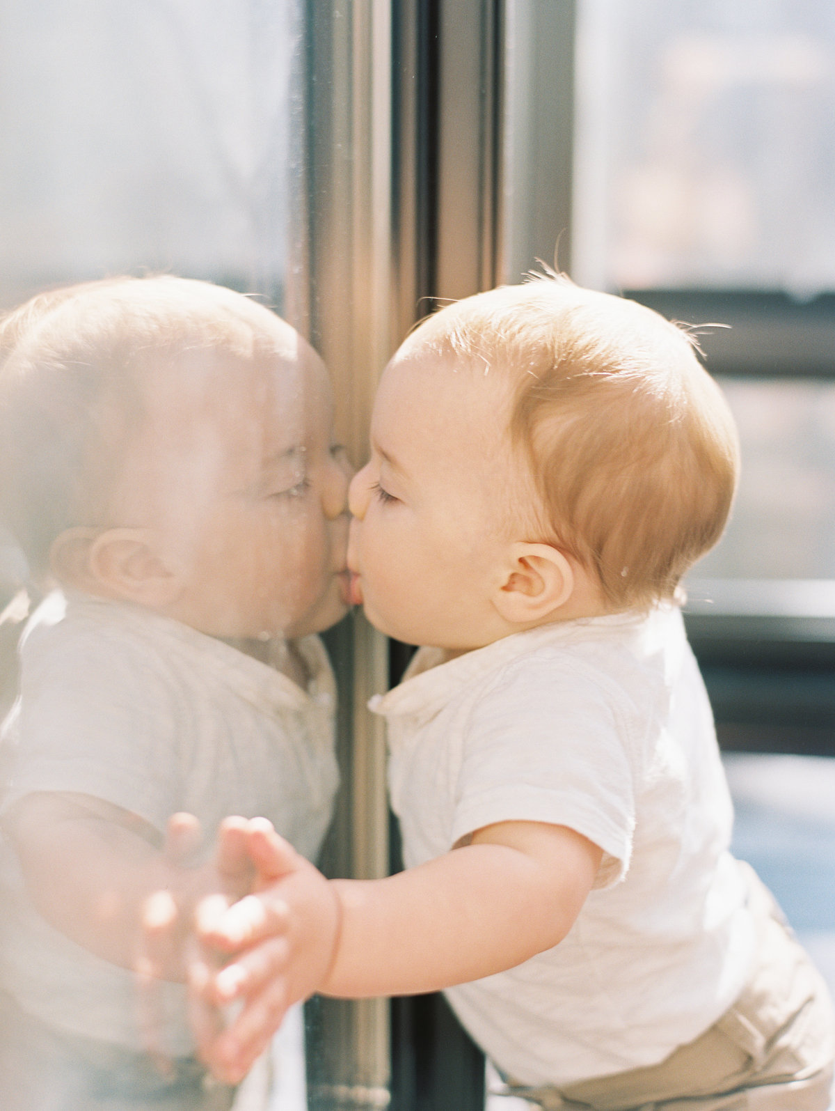 little boy kissing window