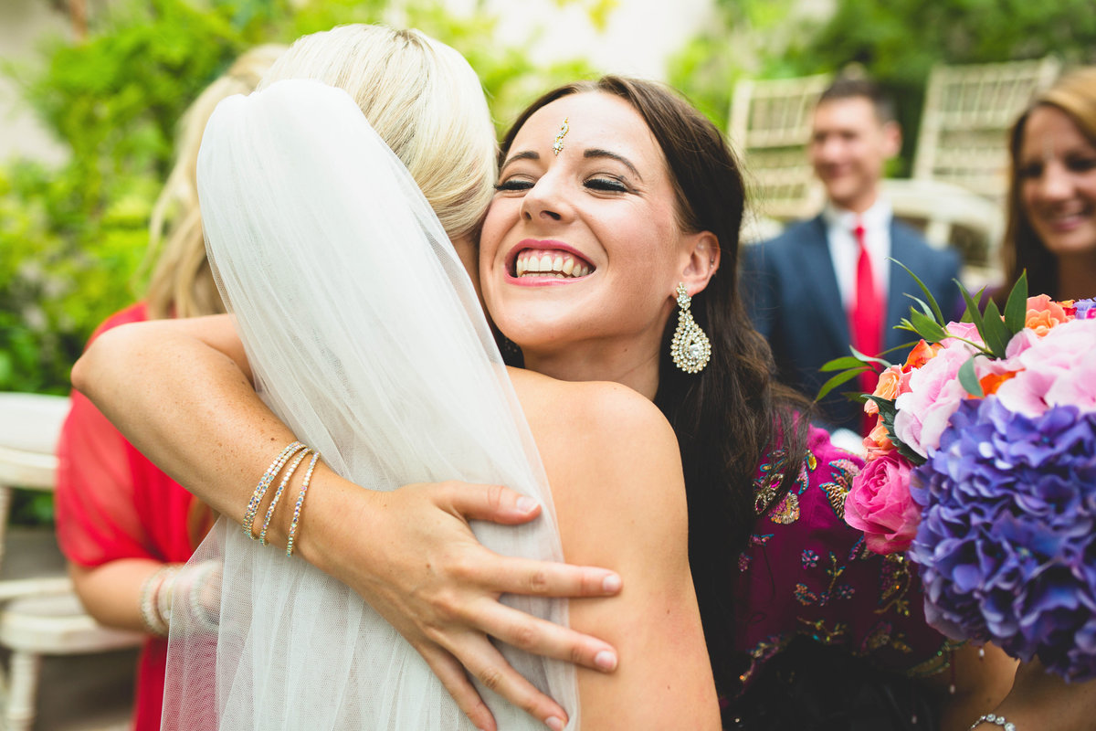 friend smiling and hugging the bride at sezincote house