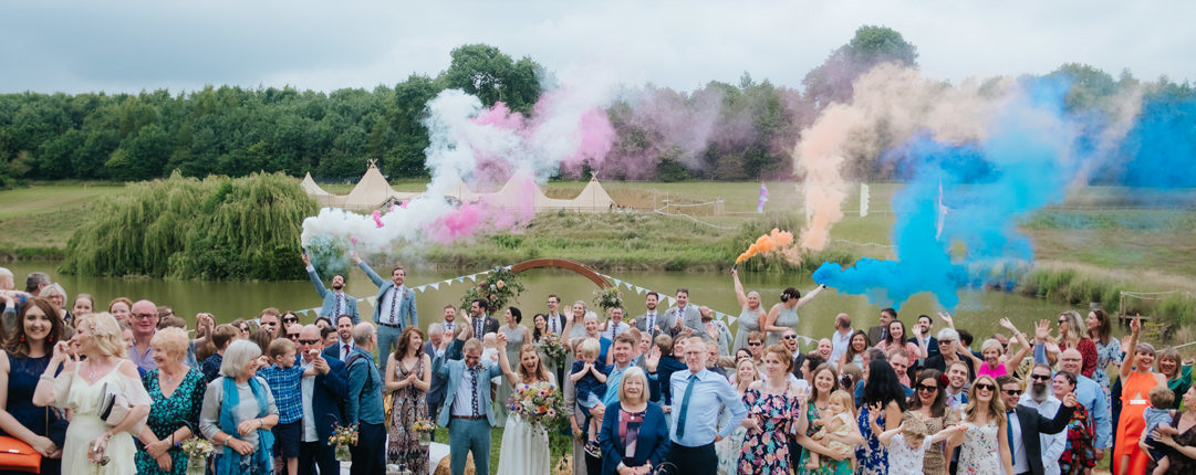 Large group of wedding guests smile at the camera for a group photo.  Colourful smoke flares are let off in the background showing plumes of orange, blue, pink and white smoke.  Hadsham Farm's lake and wedding tipi's can be seen in the background at this fun relaxed wedding