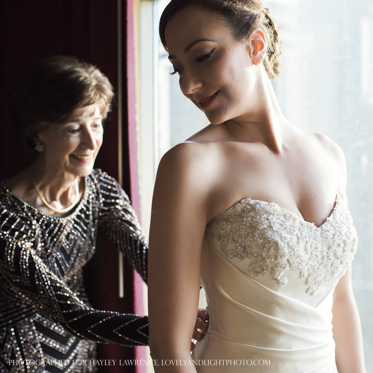 charlotte wedding photographer jamie lucido captures a beautiful moment at the hotel as the bride puts on her dress and her mother zips it from behind