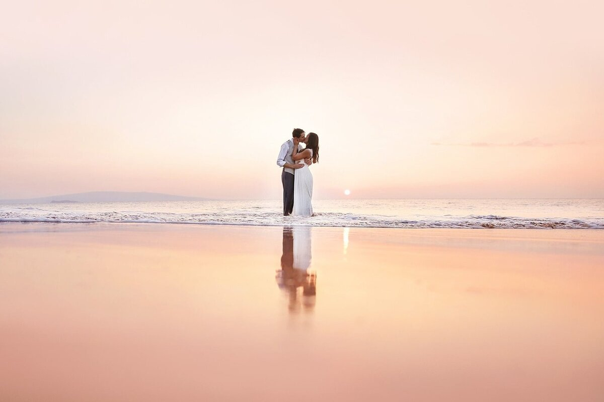 Bride and groom kiss at sunset after their Maui beach elopement