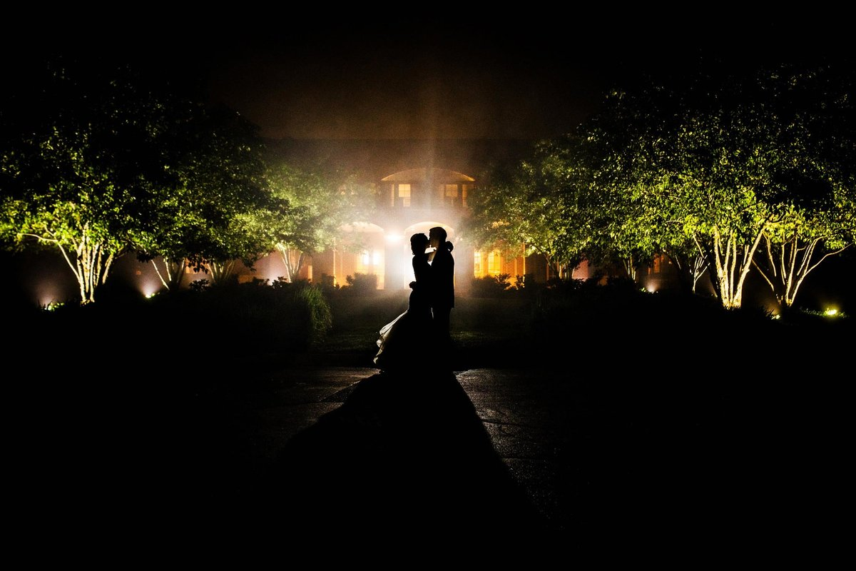 A couple kisses in silhouette during their Glen Club wedding.