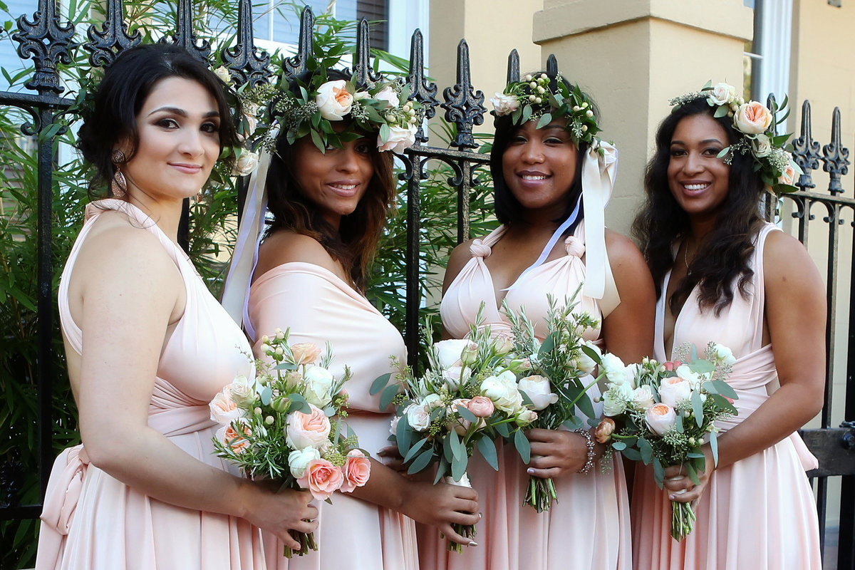 bridesmaids in front of wrought iron fence in the French Quarter