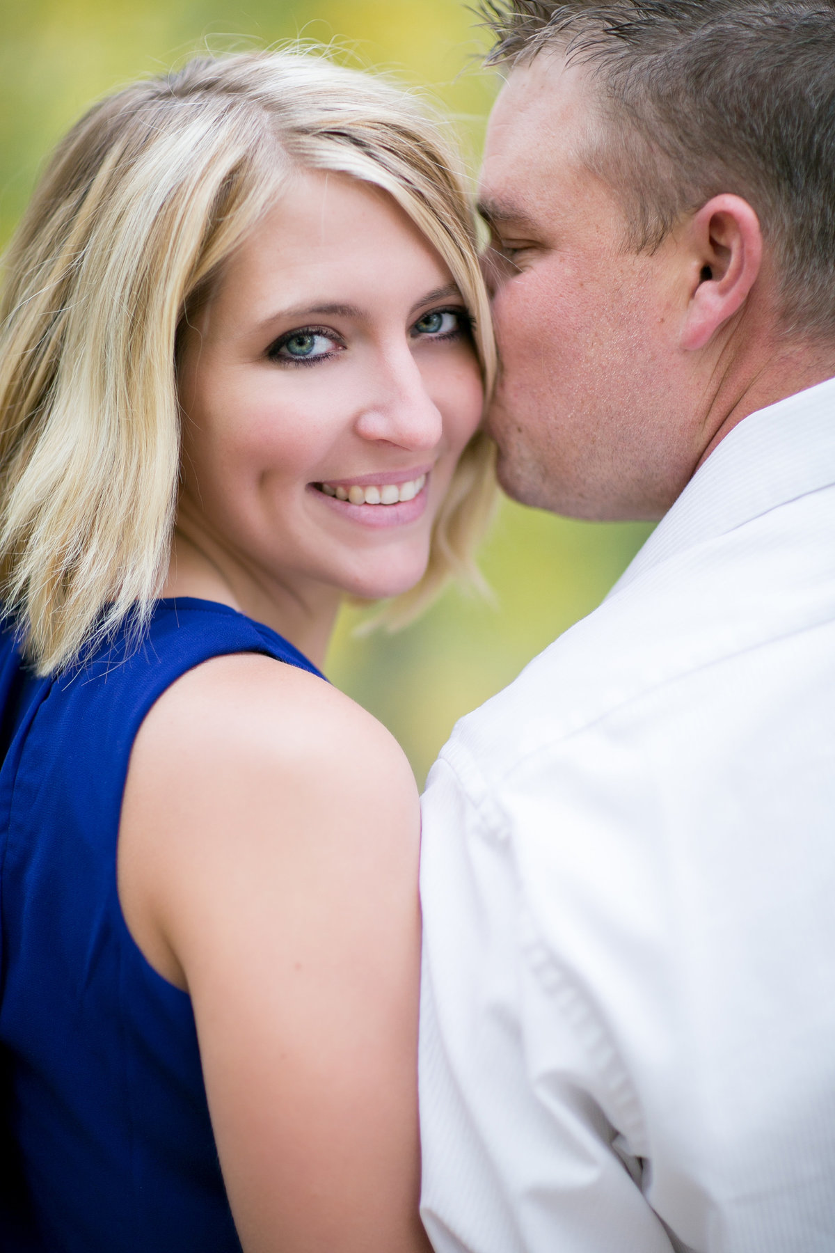 Bride in blue dress smiling at camera during longmont engagement photos