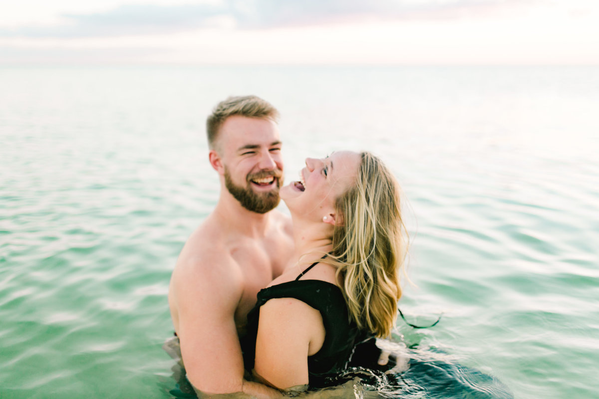 couple laughing in water at beach