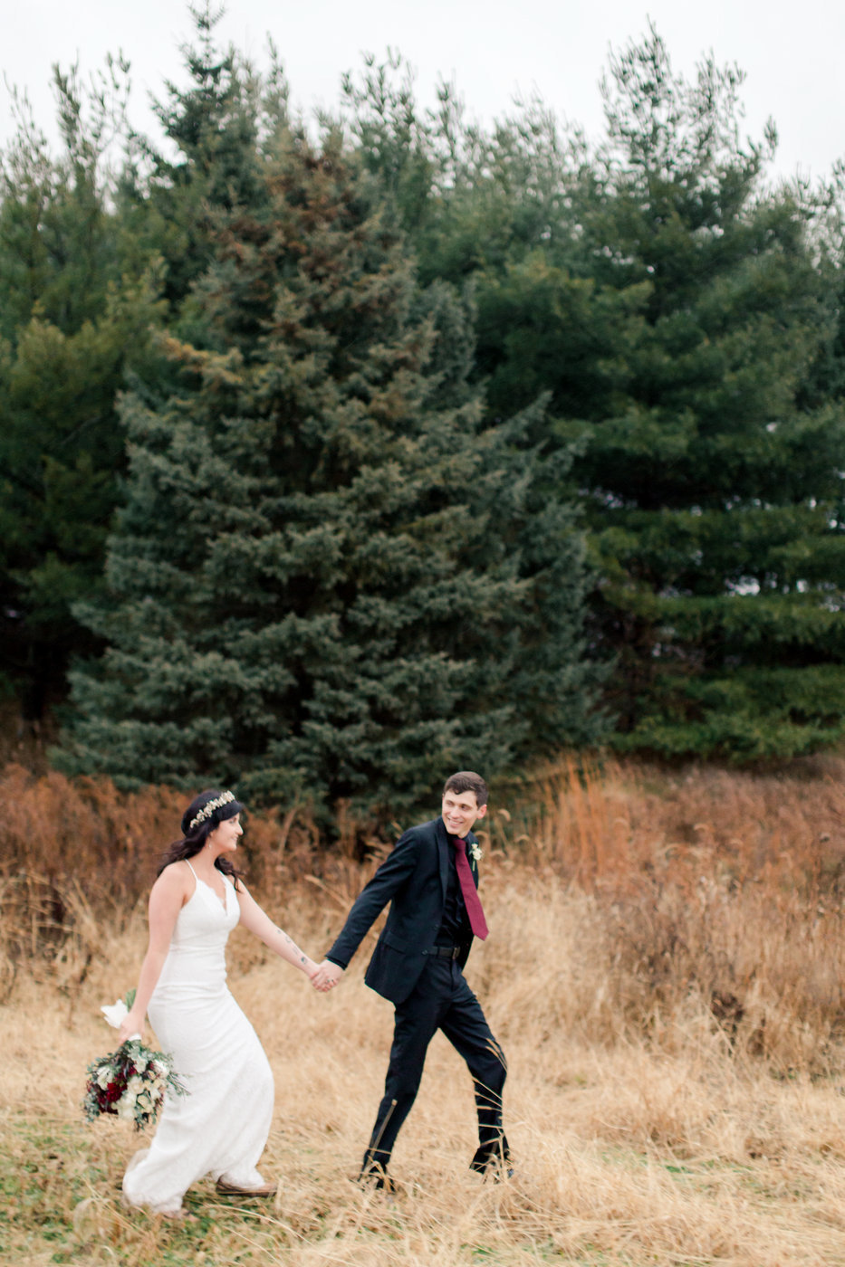 couple walks through field and spruce trees rochester minnesota elopement