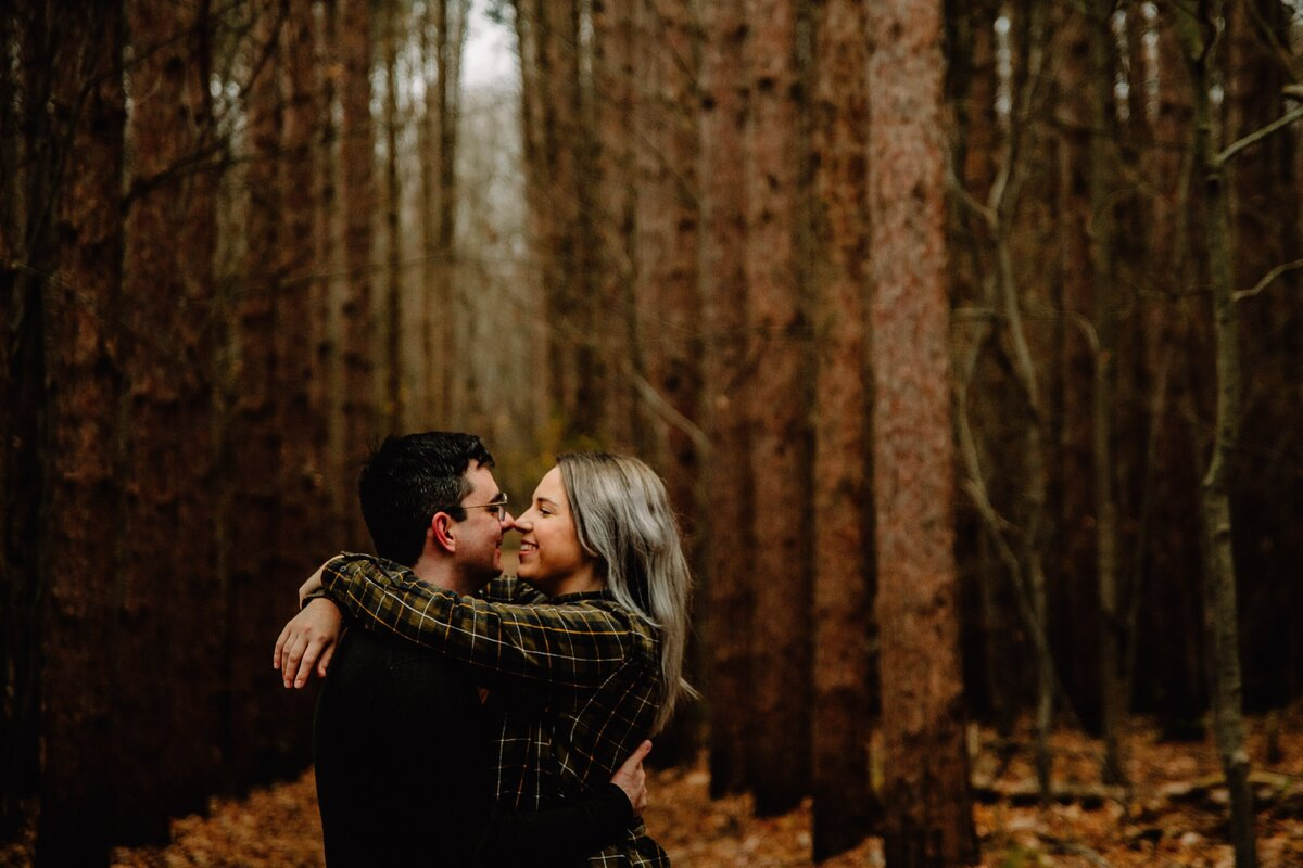 couple in woods for engagement session in kalamazoo