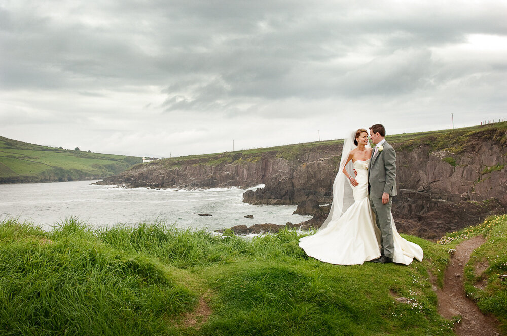bride wearing a trumpet style wedding dress with groom in grey suit standing on cliff edge with sea in the background in Dingle